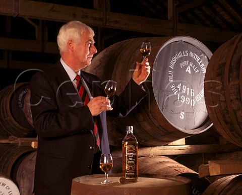 Frank McHardy Master Distiller with samples of whiskey taken from cask  a glass of 10year old malt from bottle is used to ensure consistency of the final blend  Old Bushmills Distillery Bushmills Co Antrim Northern Ireland