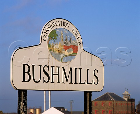 Sign at entrance to the town of Bushmills with the  Old Bushmills Whiskey Distillery in the background  County Antrim Northern Ireland