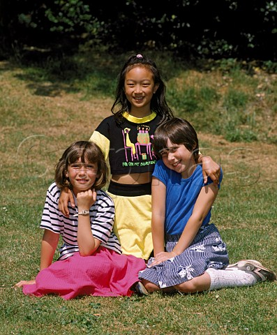 Three young girls sitting on the grass