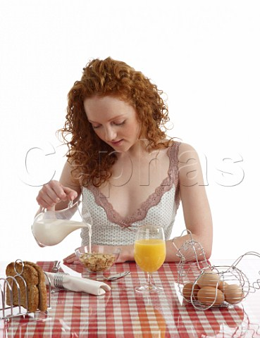 Young woman sitting at breakfast table Special K with milk wholemeal toast boiled eggs orange juice