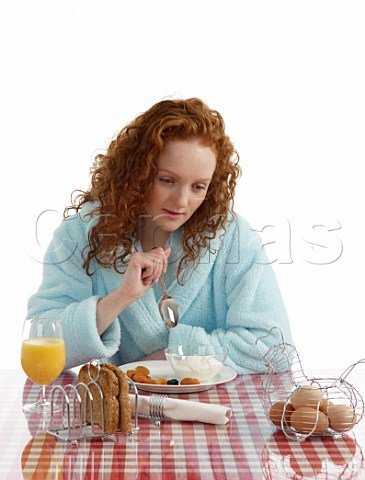 Young woman sitting at breakfast table yoghurt with dried fruits wholemeal toast boiled eggs orange juice