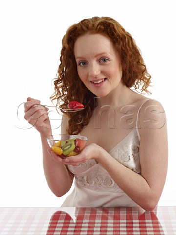 Young woman sitting at breakfast table with bowl of fresh fruit salad