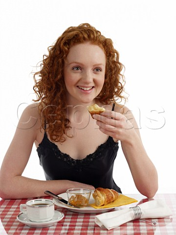 Young woman sitting at breakfast table croissant with marmalade cup of black coffee