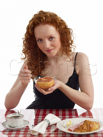 Young woman sitting at breakfast table pink grapefruit croissant with ham and butter cup of black coffee