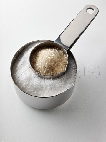 Granulated white sugar and unrefined cane sugar in steel measuring cups