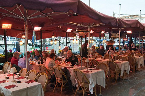 Open air restaurant seating overlooking the Grand Canal Riva del Vin Rialto Venice Italy