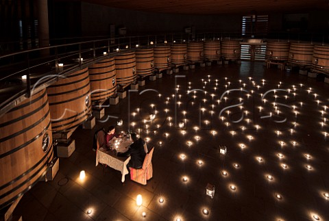 Couple having a romantic dinner in the fermentation room of Clos Apalta winery Colchagua Valley Chile